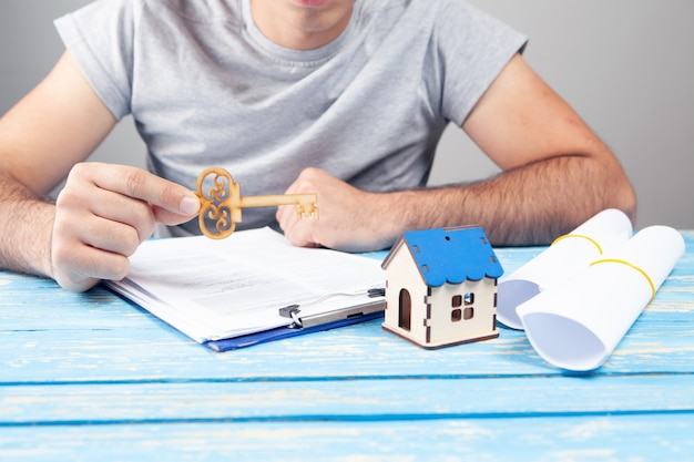 Mężczyzna trzymający klucz przed papierami i domem