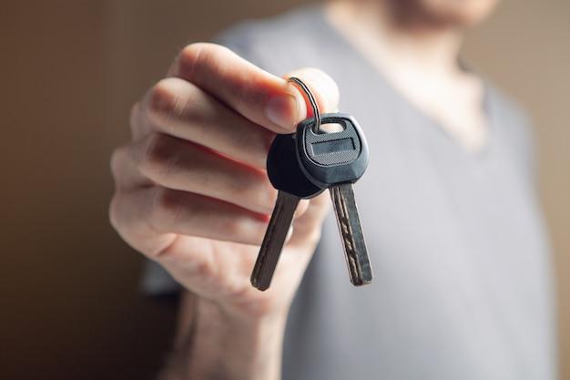 Mężczyzna trzymający klucze do domu na brązowym tle