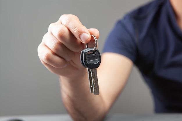 Mężczyzna trzymający klucze do domu na szaro