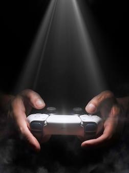Mężczyzna trzymający kontroler do gier ze światłem punktowym i mgłą