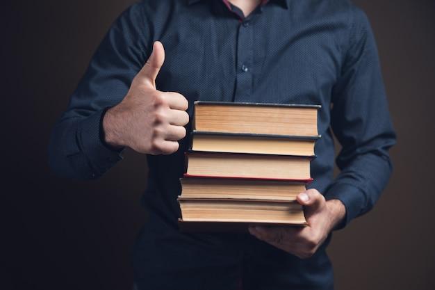 Mężczyzna trzymający książki i pokazujący kciuk na brązowej powierzchni