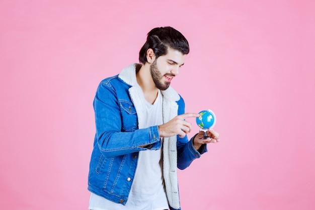 Mężczyzna trzymający kulę ziemską i próbujący znaleźć lokalizację