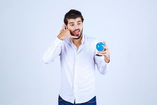 Mężczyzna trzymający kulę ziemską i proszący o telefon