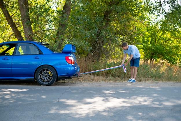 Mężczyzna trzymający linę holowniczą i mocujący ją na haku samochodowym, wypadek samochodowy i problem z silnikiem
