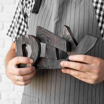 Mężczyzna trzymający litery diy wykonane z drewna z bliska