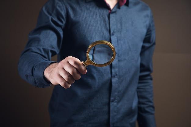 Mężczyzna trzymający lupę na brązowej powierzchni