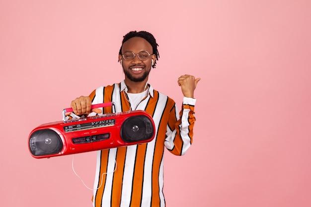 Mężczyzna trzymający magnetofon słuchający muzyki w słuchawkach wskazujących na wolną przestrzeń na reklamę