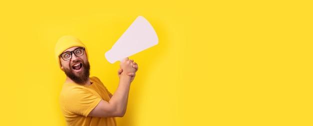 Mężczyzna trzymający megafon na żółtym tle, panoramiczny układ z miejscem na tekst