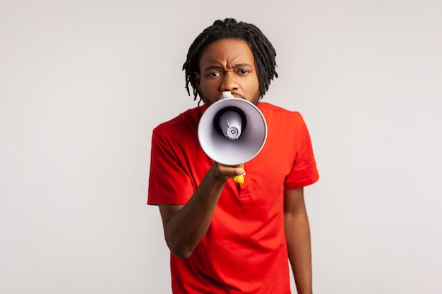 Mężczyzna trzymający megafon przy ustach głośno mówiący, krzyczący, ogłaszający, zwracając uwagę.