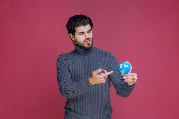 Mężczyzna trzymający mini globus i próbujący znaleźć tam miejsce.