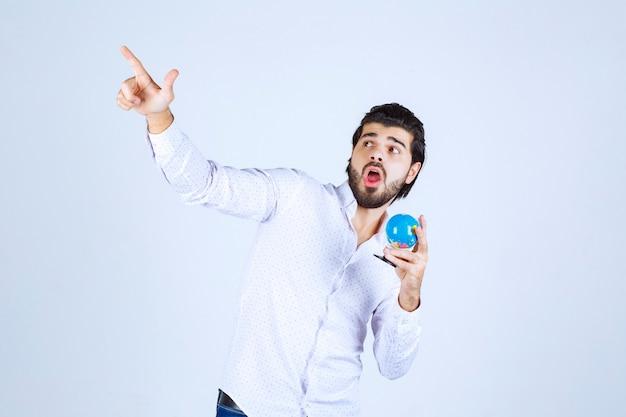 Mężczyzna trzymający mini globus i wskazujący gdzie indziej