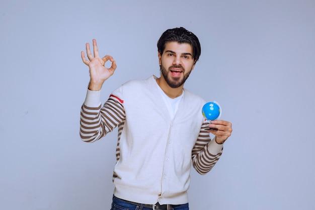 Mężczyzna trzymający mini globus i wygląda, jakby przestudiował wszystkie lokalizacje i mapę.