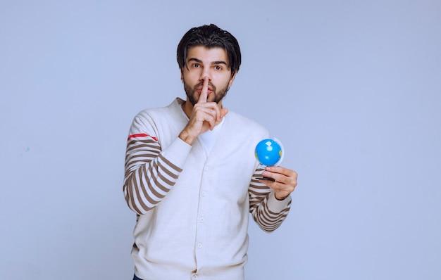Mężczyzna trzymający mini globus i wygląda na to, że nie ma wiedzy z zakresu geografii.