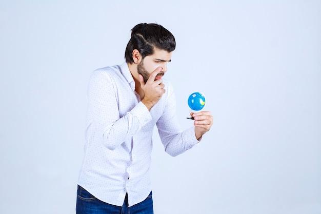 Mężczyzna trzymający mini globus i wygląda na zdezorientowanego