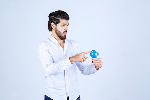 Mężczyzna trzymający mini globus i zgadujący na nim miejsce