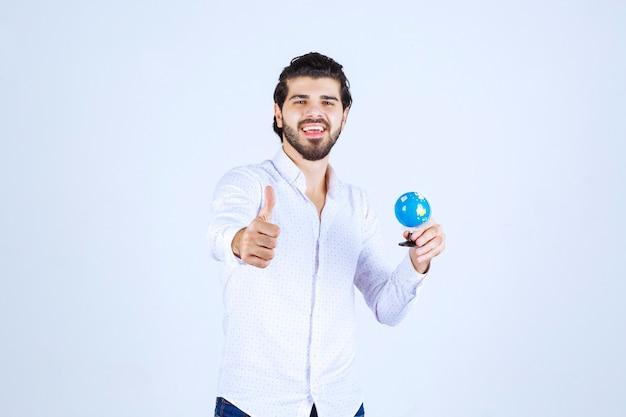 Mężczyzna trzymający mini kulę ziemską i pokazujący znak przyjemności