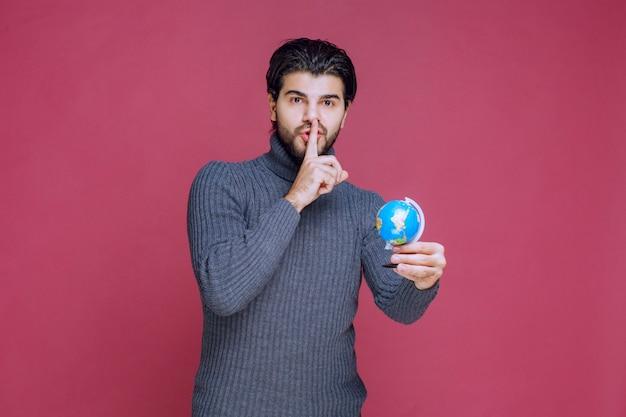 Mężczyzna trzymający mini kulę ziemską i proszący o ciszę.