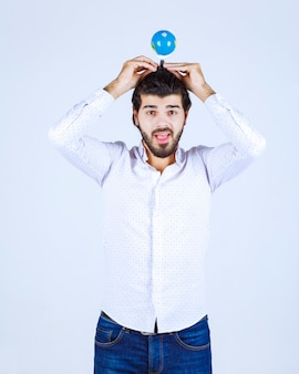 Mężczyzna trzymający mini-światową kulę ziemską