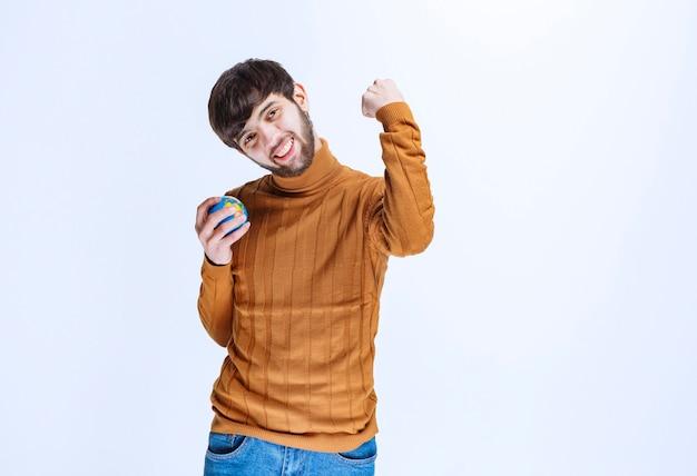 Mężczyzna trzymający minimalistyczną kulę ziemską i cieszący się nią.