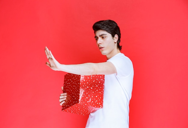 Mężczyzna trzymający mocno swoje czerwone pudełko na prezent i zatrzymujący ludzi