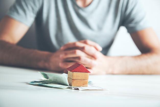 Mężczyzna trzymający model domu z pieniędzmi