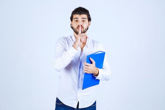 Mężczyzna trzymający niebieską teczkę i myślący