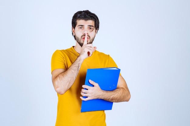 Mężczyzna trzymający niebieską teczkę i proszący o ciszę.
