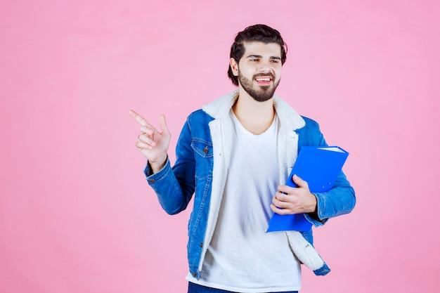 Mężczyzna trzymający niebieską teczkę i wskazujący na lewą stronę