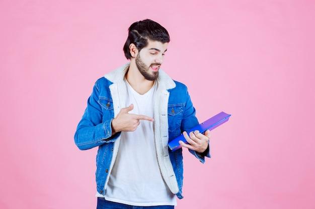Mężczyzna trzymający niebieską teczkę i wskazujący na nią