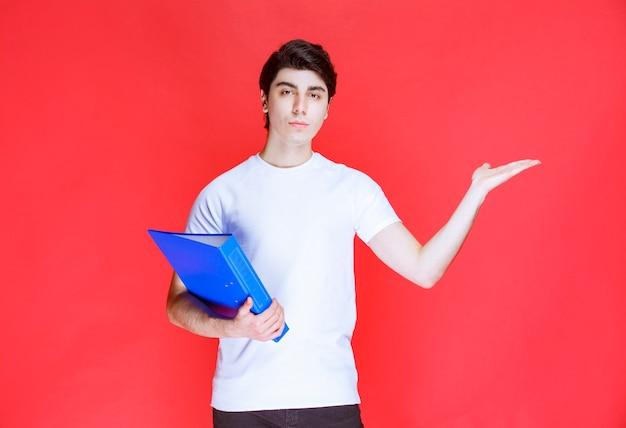 Mężczyzna trzymający niebieski folder i wskazujący gdzieś.
