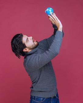 Mężczyzna trzymający niebieski mini kula ziemska i przyglądający mu się uważnie.