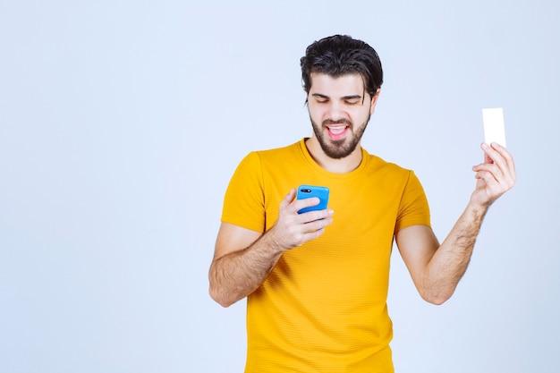 Mężczyzna trzymający niebieski smartfon i sprawdzający jego wiadomości lub dzwoniący pod numer kontaktowy na wizytówce.