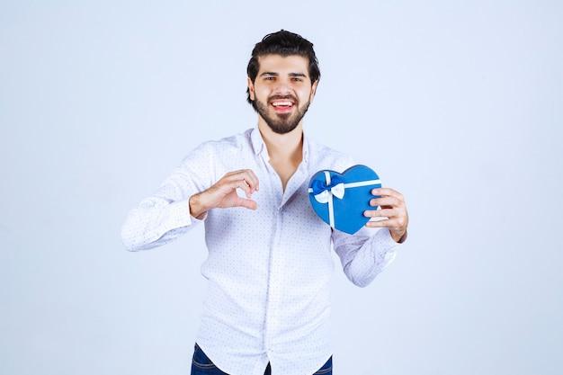 Mężczyzna trzymający niebieskie pudełko prezentowe i cieszący się nim
