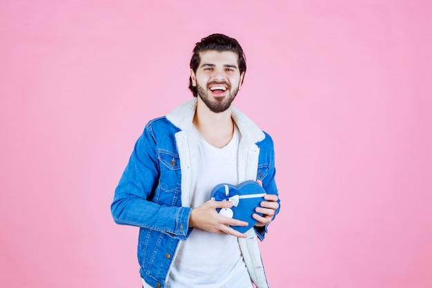 Mężczyzna trzymający niebieskie pudełko w kształcie serca i wyglądający na szczęśliwego