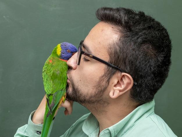 Mężczyzna trzymający papugę trichoglossus moluccanus