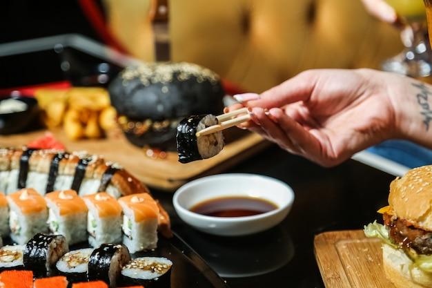 Mężczyzna trzymający patyki maguro maki imbir wasabi widok z boku