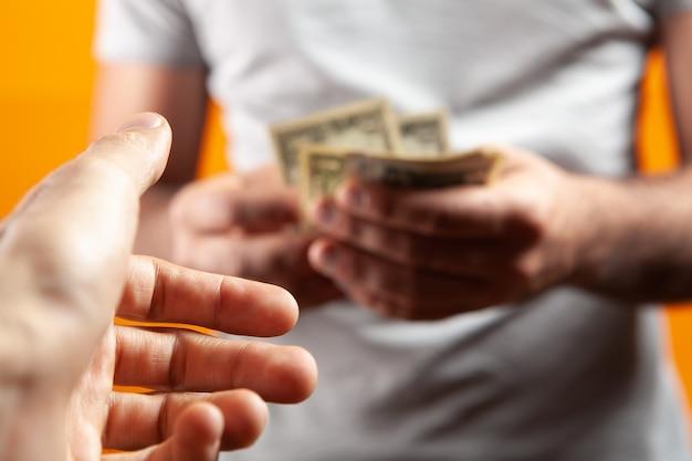 Mężczyzna trzymający pieniądze i dający drugiemu na pomarańczowym tle