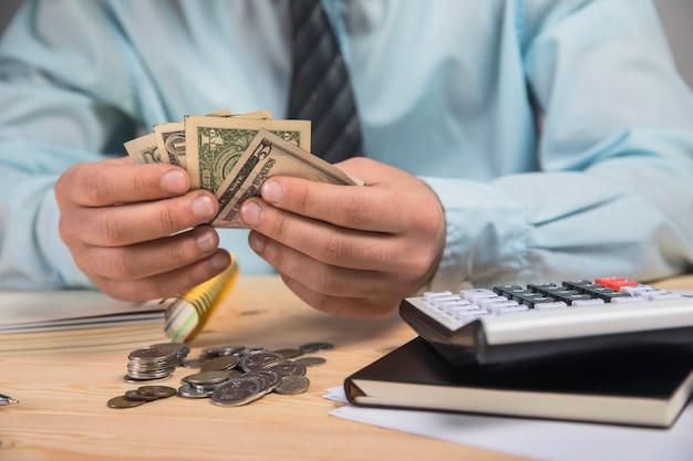 Mężczyzna trzymający pieniądze w dłoniach i liczący za pomocą kalkulatora