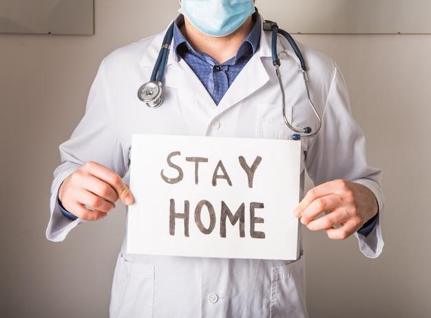 """Mężczyzna trzymający plakat z tekstem """"stay home"""" w celu zapobiegania koronawirusowi (covid-19)."""