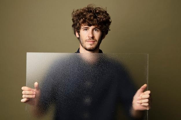 Mężczyzna trzymający półprzezroczystą szklankę przy ścianie