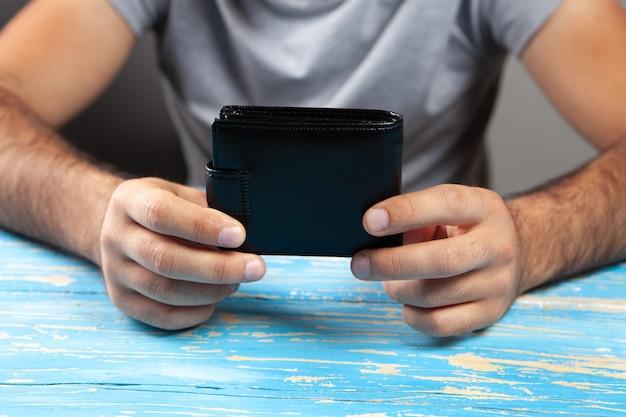 Mężczyzna trzymający portfel przy stole