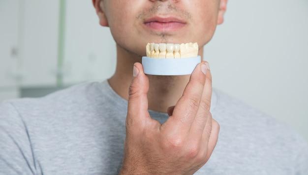 Mężczyzna trzymający pozorowaną szczękę u dentysty