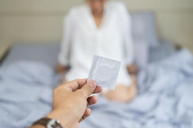 Mężczyzna trzymający prezerwatywę i przebywanie z kobietami w sypialni