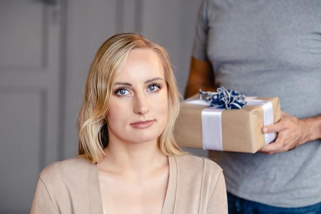 Mężczyzna trzymający przed sobą prezent, dziewczyna czekająca na niespodziankę.