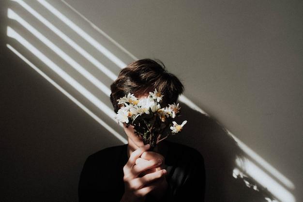 Mężczyzna trzymający przed twarzą mały bukiet kwiatów z jasnymi liniami lśniącymi na nim