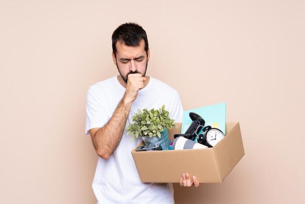 Mężczyzna trzymający pudełko i przeprowadzający się do nowego domu cierpi na kaszel i źle się czuje