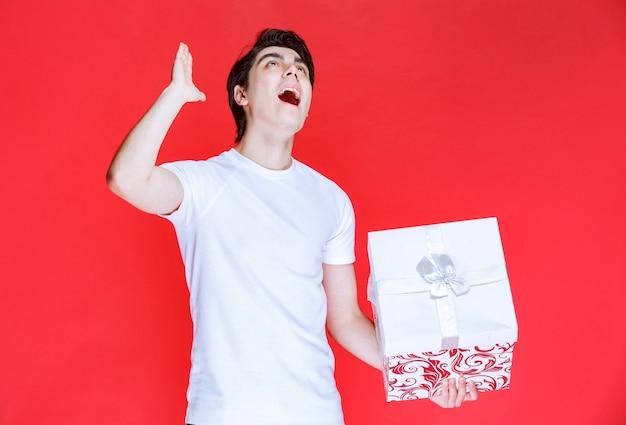 Mężczyzna trzymający pudełko, podnosząc rękę i krzycząc.