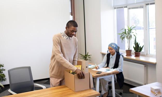 Mężczyzna trzymający pudło z rzeczami i osiedlający się w swojej nowej pracy biurowej