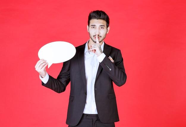 Mężczyzna trzymający pustą tablicę informacyjną w kształcie owalu i proszący o ciszę.