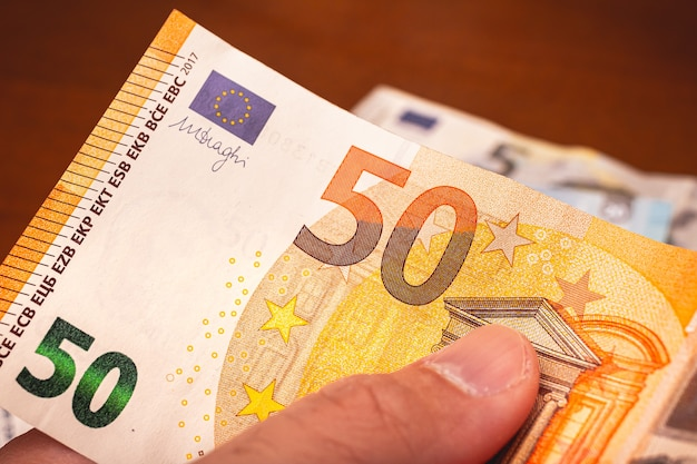 Mężczyzna trzymający rachunek w wysokości 50 euro na biznes finansowy i koncepcje zarabiania pieniędzy